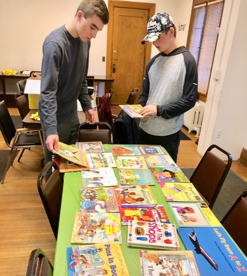 Ben and Sam sorting books left behind from the days when the building served as a day care center. Books will be donated to a library.