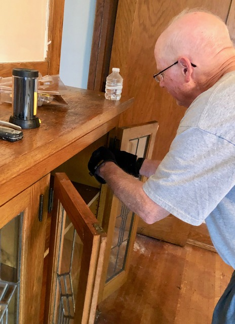 Greg removing book cabinet leaded-glass paneled doors for preservation safekeeping on-site.