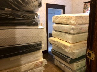 Mattresses moved up tight stairways to first floor for later distribution to rooms. All mattresses have clean protective covers.