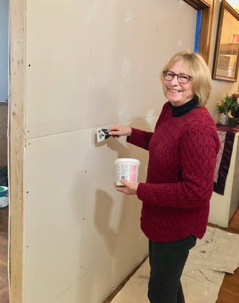 Sarah applying finishing touches to wall privacy addition. Special care taken to preserve original wood surfaces