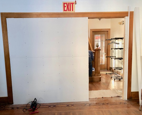 Wall affords privacy but will permit easy egress. Looking outward to west exit. The four leaded-glass doors formerly occupying this space are stored for safe-keeping.